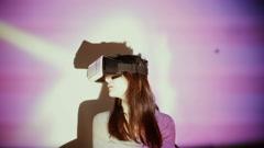 Woman using VR-helmet in the spotlight Stock Footage