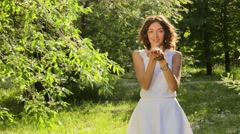 Beautiful Woman Blowing Dandelion Seeds - stock footage