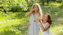 Beautiful young mother together with her daughter in nature making soap bubbles - stock footage