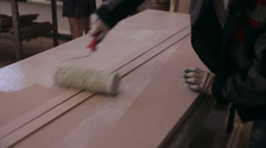 Man hand paints, glueing a wooden parts. Door production factory Stock Footage
