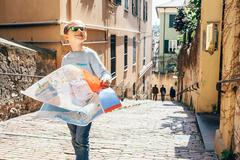 Little boy with city map stay on the old italian street Stock Photos