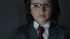 4k shoot of a cute child posing as a business man in studio putting glasses Stock Footage