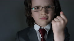 4k shoot of a cute child posing as a business man in studio putting glasses - stock footage