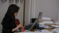 Woman with glasses working at a desk using a laptop Stock Footage