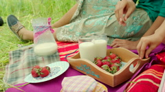 Young girls eating strawberry and drinking milk Stock Footage