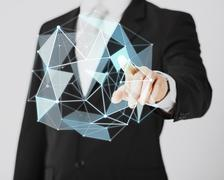 man pointing at virtual low poly projection - stock photo
