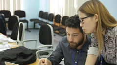A man with a beard and a woman of asian appearance with glasses work together in Stock Footage