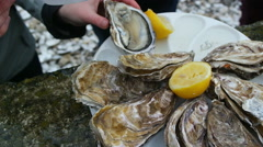 Man opens an oyster and waters it with lemon juice Stock Footage