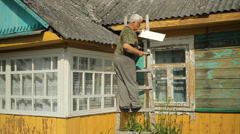 A man tries to fix the roof. He is standing on the stairs near the house Stock Footage