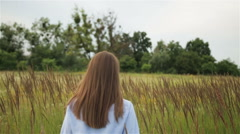 Girl in a blue shirt talking on the field. Stock Footage