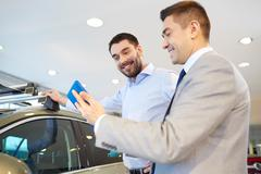 happy man with car dealer in auto show or salon - stock photo