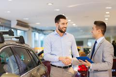 happy man shaking hands in auto show or salon - stock photo
