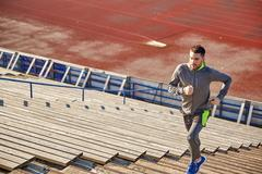 young man running upstairs on stadium - stock photo