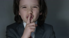 4k shoot of a cute child posing as a business man in studio showing shush  Stock Footage