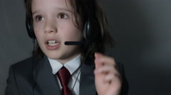 4k shoot of a cute child posing as a business man in studio - Customer Support - stock footage