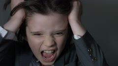 4k shoot of a cute child posing as a business man in studio screaming angry Stock Footage