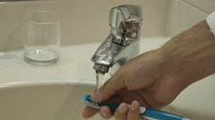 Wash the toothbrush under running water Stock Footage