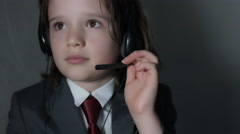 4k shoot of a cute child posing as a business man in studio - Customer Support Stock Footage
