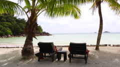 Sunny and tropical beach view with deckchairs, Seychelles Stock Footage
