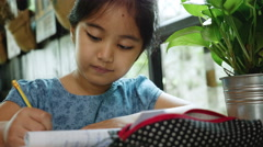 4K : Little Asian child doing her exercise workbook, Pan shot Stock Footage