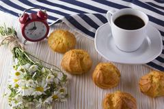 Eclair, coffee cup, alarm clock and charmomile. Stock Photos