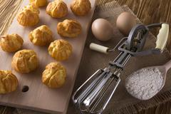 Tasty eclairs, eggs, flour and handle mixer. Stock Photos