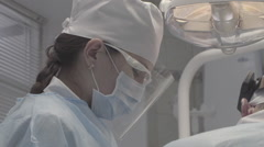 Dental surgery. The nurse assists the doctor, not color corrected, good for Stock Footage