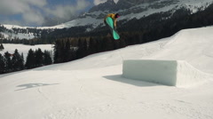 Following model snowboarder doing a big jump Stock Footage
