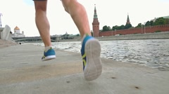 Slow motion steadicam shot of athletic male runner legs against Moscow Kremlin Stock Footage