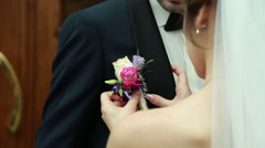Bride putting on flower boutonniere on groom in black suit Stock Footage