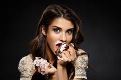Picture of funny woman in creamy dress holding piece of cake Stock Photos