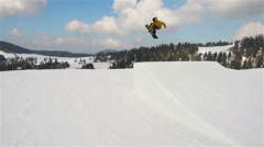 Following snowboarder doing big jump slw motion Stock Footage