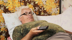Senior man in the bed at home with TV remote control Stock Footage