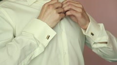 A groom putting on cuff-links as he gets dressed in formal wear .Groom's suit Stock Footage