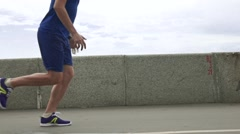 Athletic man running against river bank parapet and sky. Super slow motion Stock Footage