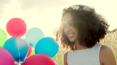Young girl wearing flower wreath with colour balloons in sunset Stock Footage