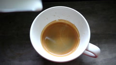Pouring stream milk into a cup of espresso, slow motion Stock Footage