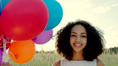 Young girl with colour balloons in sunset Stock Footage