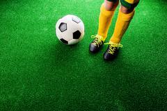 Unrecognizable little football player against green grass, studi Stock Photos