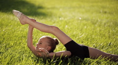 Petite flexible girl does in the grass complex gymnastic exercises. - stock footage