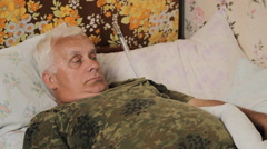 Senior man sick in bed with a huge thermometer. Funny thermometer under his arm Stock Footage
