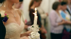 Wedding ceremony in orthodox church. Bride and groom holding the candles. Close - stock footage