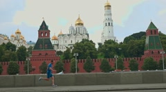 Slow motion steadicam shot of a sportsman running against Moscow Kremlin 120 fps Stock Footage