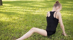 Young girl doing gymnastics yoga and stretching in the city park on sunset Stock Footage