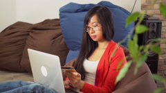 Young asian woman buy online on the computer sitting on the bean bag chair Stock Footage