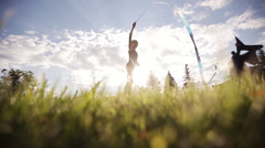 Rhythmic gymnastics. Dance young gymnast with ribbon on sunset sky background. - stock footage