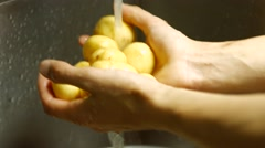 Male hands washing potatoes. - stock footage