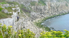 4K Long shot of young man climbing rocky cliff on the English coastline Stock Footage