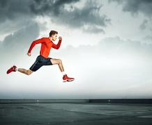 Young handsome athlete running - stock photo