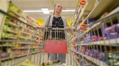 Caucasian woman walking along wholesale shelves and taking goods in shop trolley Stock Footage
